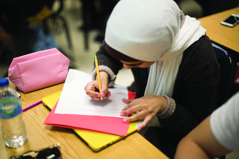 Female student writing in creative writing class