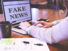 person at computer with the words 'fake news'