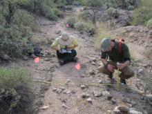 Two people record the physical attributes of a trail