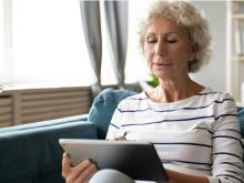 older women holding laptop