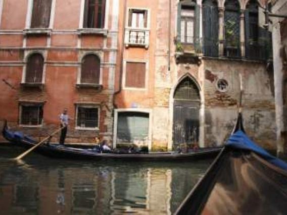 Gondola on canal between buildings in Italy