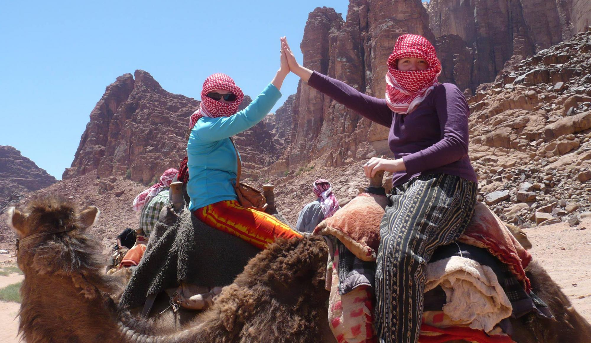 Two students wearing head scarves high-fiving as they ride camels
