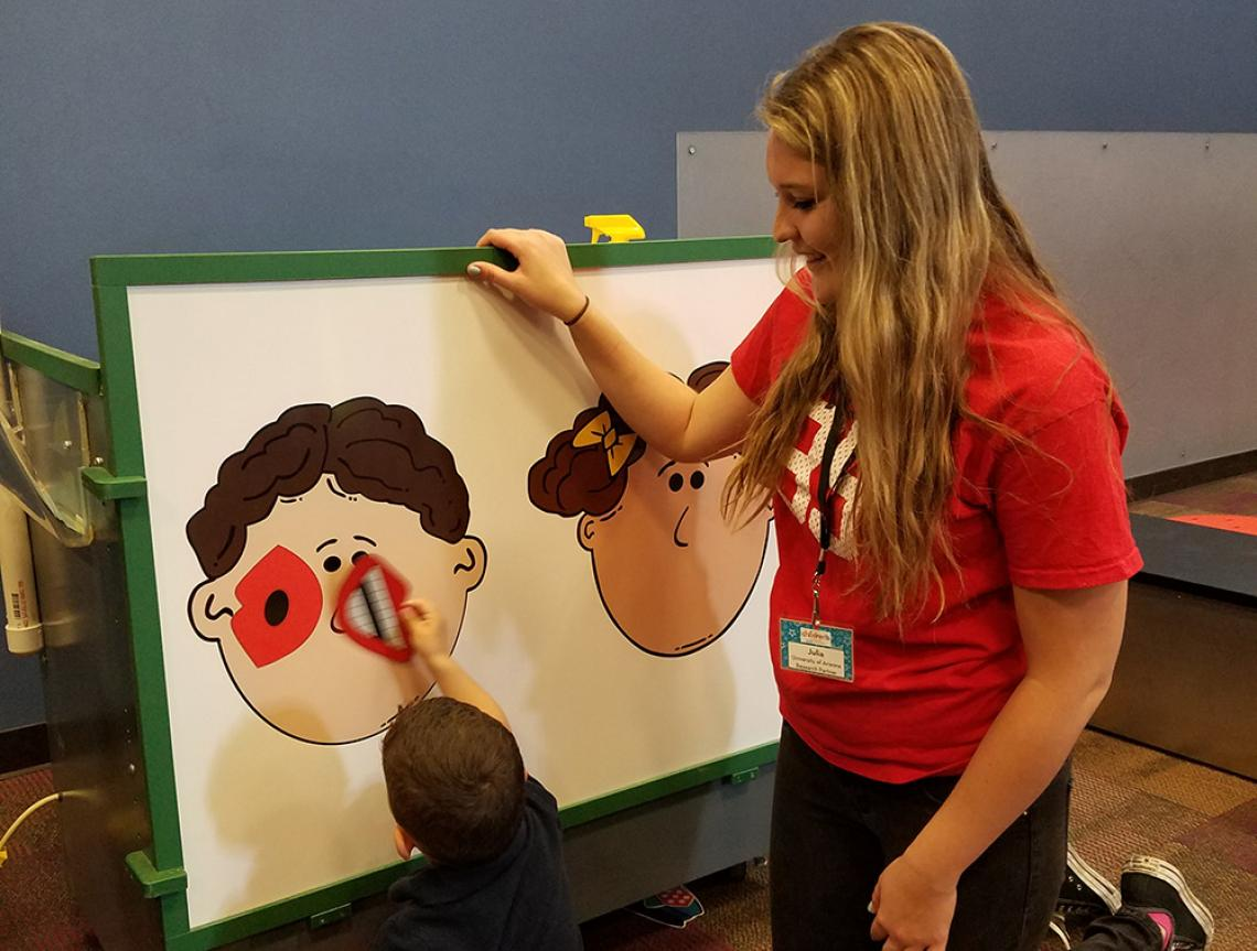 Linguistics student working with kids at Children's Museum