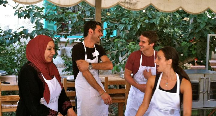 four people cooking
